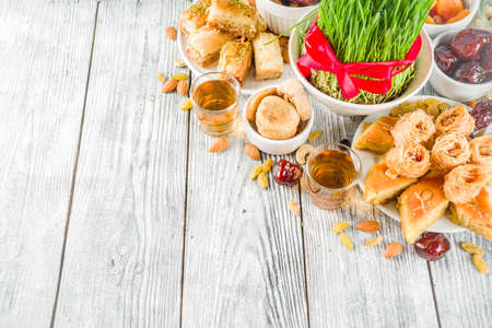 Happy Nowruz holiday background. Celebrating Nowruz sweets and treats- baklava, various dried fruits,  nuts, seeds, wooden background with green grass, copy space