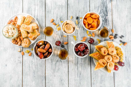 Set various Middle Eastern Arabian sweets - Turkish baklava, knafeh (kunaf), nuts, dried fruits and seeds. White wooden background, top view copy space Banco de Imagens