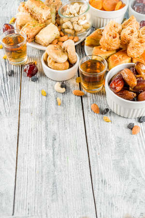 Set various Middle Eastern Arabian sweets - Turkish baklava, knafeh (kunaf), nuts, dried fruits and seeds. White wooden background, top view copy space Banco de Imagens - 118617268