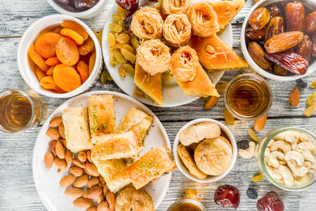 Set various Middle Eastern Arabian sweets - Turkish baklava, knafeh (kunaf), nuts, dried fruits and seeds. White wooden background, top view copy space 스톡 콘텐츠