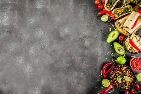 Cinco de Mayo Food.Mexican Food Konzept Hintergrund mit Taco, Quesadilla, Burrito, Chili, Salsa-Sauce, Peperoni, Limette. Schwarzer Betonhintergrund Draufsicht Kopie Raum Standard-Bild