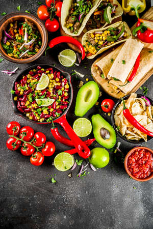 Cinco de Mayo food.Mexican food concept background with taco, quesadilla, burrito, chili, salsa sauce, hot pepper, lime. Black concrete background top view copy space