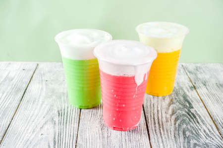 Summer colorful iced fog tea drinks, with tea, honey, matcha, lemonade,with foamed milk, wooden background copy space
