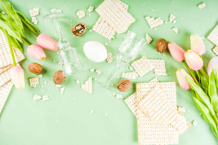 Pesah celebration concept. jewish Passover holiday background with matzo, eggs, spring flowers, wine, green background copy space top view Stock Photo