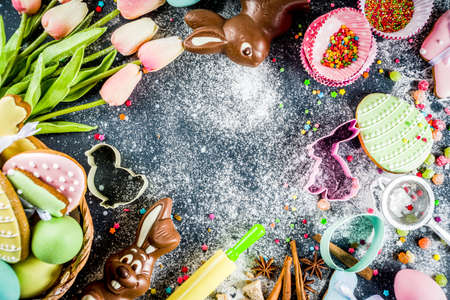 Easter greeting card background. Cooking gingerbread cookies ingredients, With colorful eggs. cookies and sugar sprinkles top view copy space Stock Photo