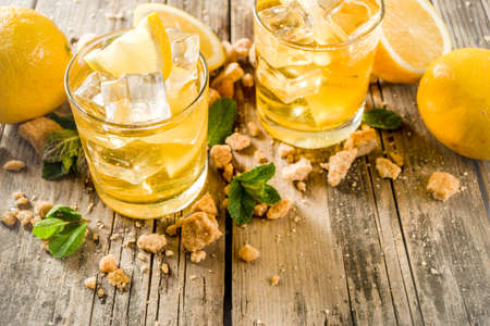 Lemonade or iced summer tea, with fresh lemon slices, sugar and mint leaf, rustic wooden table, copy space Stock Photo