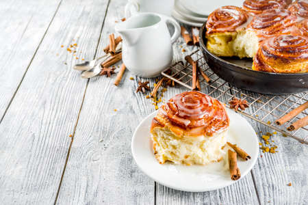 Homemade baking, Cinnamon rolls with sugar frosting. With cinnamon sticks and spices, wooden background copy space 写真素材