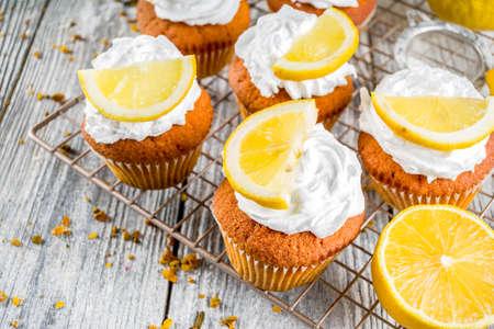 Hausgemachte Zitronen-Cupcakes, süß-saures Backgebäck, mit frischen Zitronenscheiben, Holzhintergrund-Kopierraum Standard-Bild
