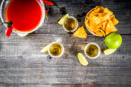 Cinco de Mayo celebration concept. 5th May Mexican party's drinks - margarita cocktail, tequila shots with lime, hot chili peppers and chips, dark background copy space
