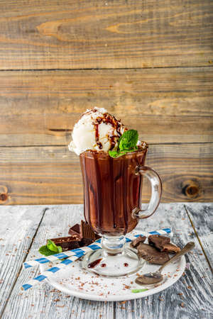 Iced chocolate cocktail. Cold summer sweet drink with cocoa, vanilla ice cream ball and mint leaves. wooden background copy space