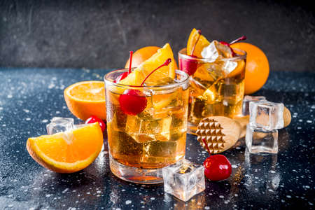 Classic alcohol cocktail, whiskey with ice cubes, orange slices and cocktail red cherries. In two glasses, on a dark blue concrete table,