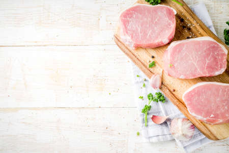 Cooking meat dinner background. Raw fresh meat, pork brisket boneless steak, with spices, herbs, olive oil, on a white wooden background, top view 스톡 콘텐츠