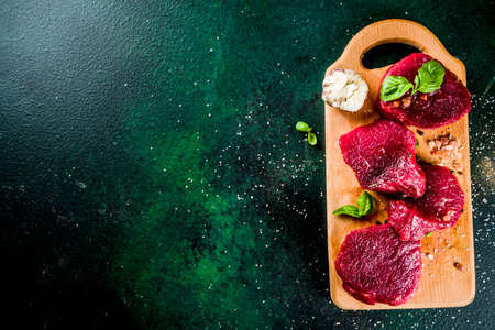 Raw beef meat steaks, with olive oil and spices, dark green concrete background copy space top view