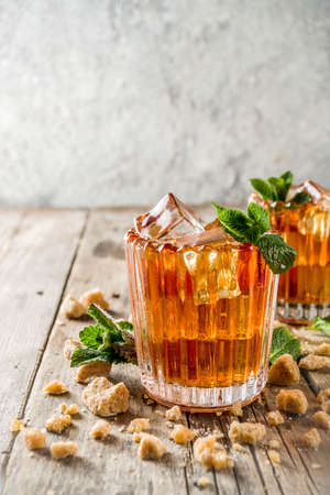 Summer iced mint tea. Traditional Moroccan drink  with mint. Rustic wooden background, copy space