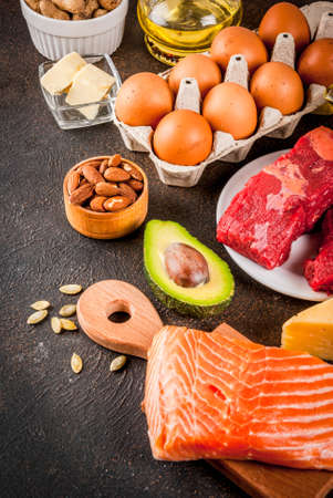 Ketogenic low carbs diet concept. Healthy balanced food with high content of healthy fats. Diet for the heart and blood vessels. Organic ingredients, dark rusty background, copy space Stock Photo