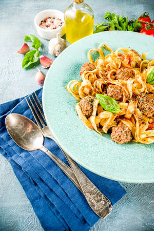 Italian fettuccine pasta with meatballs in tomato sauce in a portioned plate on light blue concrete background.Top view copy space