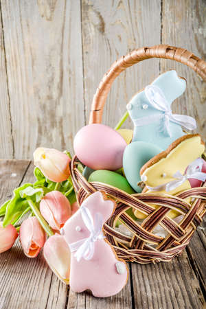 Easter holiday greetings background, basket with pastel colored eggs, Easter baking cupcake cookies, spring flowers. Wooden rustic background, copy space