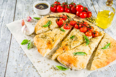 Traditional  homemade Italian flat bread focaccia. Focaccia with tomatoes and basil leaves, wooden background, top view Imagens