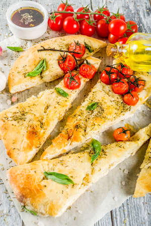 Traditional  homemade Italian flat bread focaccia. Focaccia with tomatoes and basil leaves, wooden background, top view Stock Photo