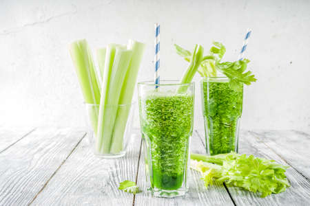 Healthy vegan food and drink. Diet green cucumber and celery smoothie cocktail, on a wooden background, Stockfoto
