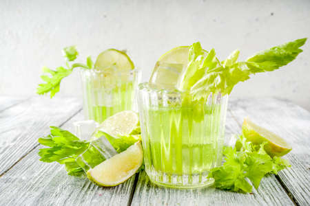 Celery Daisy Cocktail. Fresh summer drink, mojito, iced lemonade or margarita with celery and lime slices, wooden background copy space