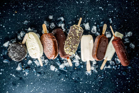 Assortment of various  ice cream, vanilla and chocolate, with nuts, on a dark concrete background with ice, copy space top view