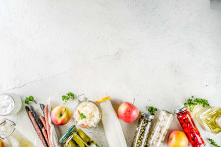 Assortment of various fermented food - apple cider vinegar, fermented meat and vegetables,  sauerkraut, pickled peppers, tomatoes, garlic, capers, white background copy space
