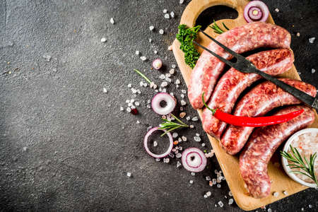 Homemade raw beef and pork sausages for bbq grilling, with herbs and spices, black concrete background top view copy space