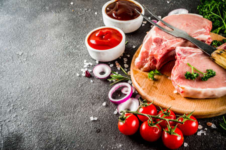 Raw meat, pork steaks, ready for cooking, with herbs, black concrete background copy space