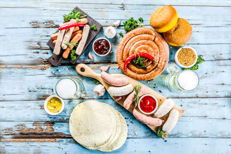Different bbq picnic party food with beer various grilled sausages, burger buns, flat taco bread, beer, old wooden background copy space Foto de archivo