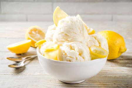 Homemade lemon vanilla ice cream with fresh lemon slices. Sweet and sour summer dessert. Wooden background copy space