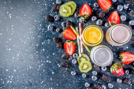 Summer fruits and berries smoothie drink. Vitamin diet snack beverage, with blueberries, strawberries, blackberries, kiwi. Dark blue concrete background copy space Stock Photo