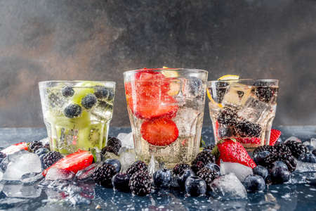 Summer fruits and berry cold cocktail, Lemonade, infused water with blueberries, strawberries, blackberries, kiwi. lemon. Dark blue concrete background copy space Stock Photo