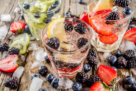 Summer fruits and berry cold cocktail, Lemonade, infused water with blueberries, strawberries, blackberries, kiwi. lemon. Rustic wooden background copy space Stock Photo