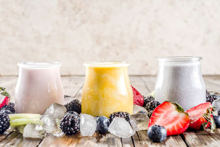 Summer fruits and berries smoothie drink. Vitamin diet snack beverage, with blueberries, strawberries, blackberries, kiwi. Dark blue concrete background copy space Stock Photo