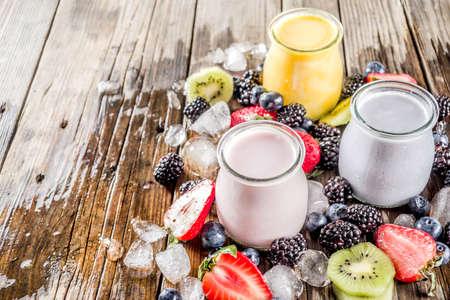Summer fruits and berries smoothie drink. Vitamin diet snack beverage, with blueberries, strawberries, blackberries, kiwi. Dark blue concrete background copy space
