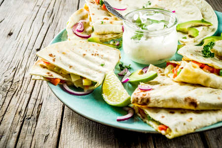 Mexican traditional food, quesadilla with chicken and vegetables, with white sauce, rustic wooden background copy space