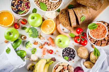 Gesundes Essen. Auswahl an guten Kohlenhydratquellen, ballaststoffreiche Nahrung. Diät mit niedrigem glykämischen Index. Frisches Gemüse, Obst, Getreide, Hülsenfrüchte, Nüsse, Grüns. Textfreiraum aus weißem Marmor Standard-Bild