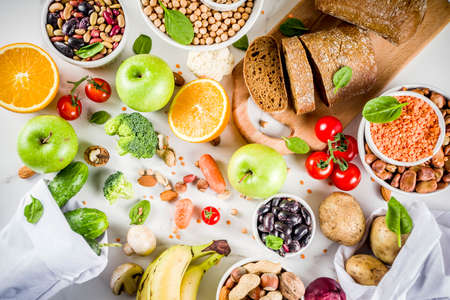 Gezond eten. Selectie van goede koolhydraatbronnen, vezelrijk voedsel. Lage glycemische index dieet. Verse groenten, fruit, granen, peulvruchten, noten, groenten. Witte marmeren achtergrond kopie ruimte Stockfoto
