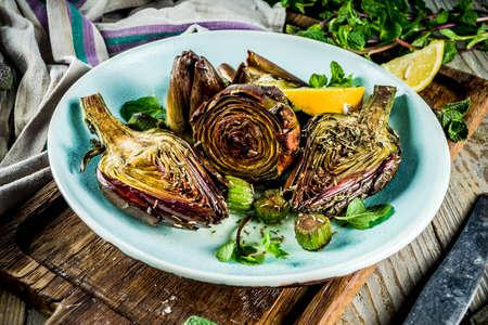 Carciofo cotto al forno, alla romana, fiori di carciofo grigliati con olio d'oliva, limone, aglio, menta e spezie. Copia spazio