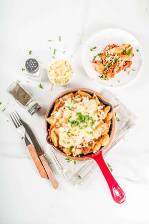 Baked creamy pasta casserole, mac and cheese with minced meat, italian ground beef bolognese casserole, dark blue concrete background copy space