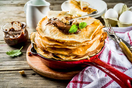 Homemade crepes with chocolate sauce, russian and ukrainian thin pancakes bliny, rustic wooden background copy space