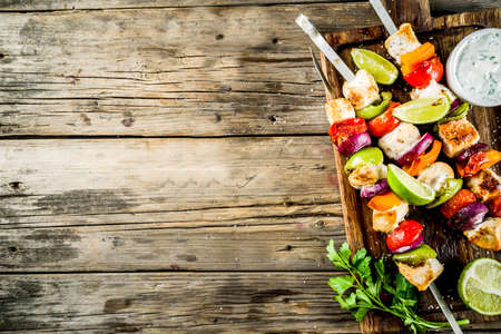 Grilled chicken skewers kebabs with vegetables, on rustic wooden table top view copy space