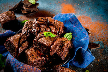 Homemade chocolate brownies with chocolate powder and mint leaves on dark background, top view copy space Banque d'images