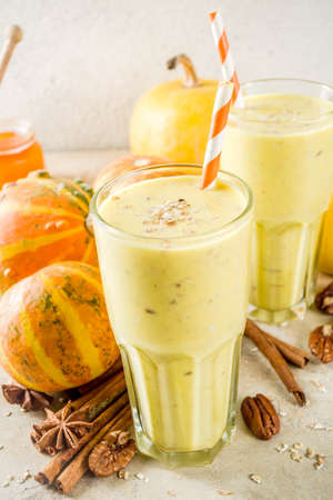 Healthy breakfast, snack. Spicy pumpkin smoothie with pumpkins, pecan nuts, honey, oatmeal, cinnamon, anise. Light concrete background copy space