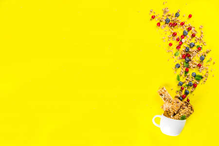Small cup with breakfast oat granola, cereal muesli, nuts and berries. Healthy breakfast or snack concept, Bright trendy background, Top view copy space