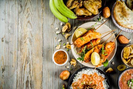 West african food concept. Traditional Wset African dishes assortment - peanut soup, jollof rice, grilled chicken wings, dry fried bananas plantains, nigerian chicken kebabs, meat pies, top view Stock Photo