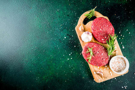 Raw beef burger cutlets, with spices and herbs, dark concrete background copy space