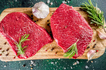 Raw beef meat steaks with spices and herbs, dark concrete background copy space