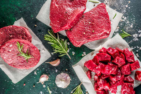 Various raw beef meat with spices and herbs, dark concrete background copy space Reklamní fotografie